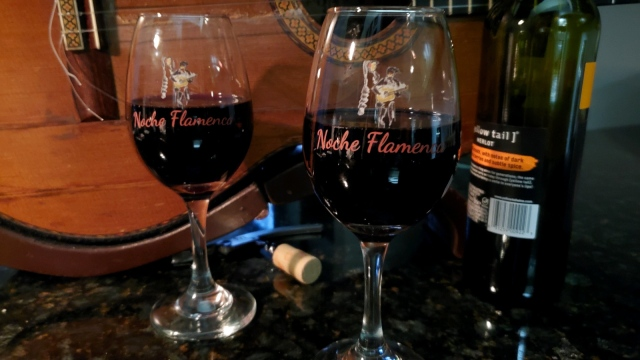 Two Noche Flamenca wine glasses, half full of red wine, stand in front of a guitar laying on its side.